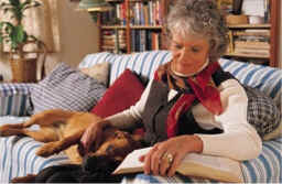 woman reading on couch with dog